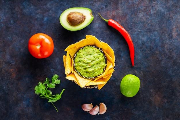 Sos guacamole z awokado, papryką, limonką i nachosami kukurydzianymi na ciemnym tle. guacamole z dodatkami i chipsami tortilla nachos. skopiuj miejsce