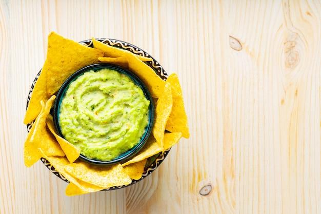 Sos guacamole z chipsami kukurydzianymi na drewnianym tle. chipsy tortilla i meksykański sos guacamole w misce. skopiuj miejsce. widok z góry