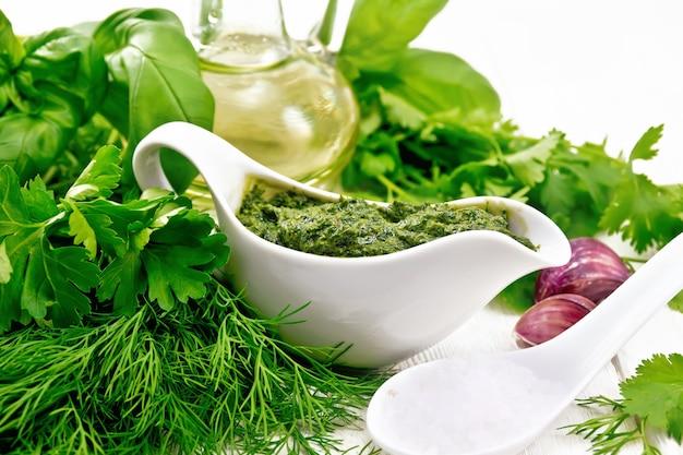 Sos koperkowy, pietruszka, bazylia, kolendra, inne pikantne zioła, czosnek i olej roślinny w sosie własnym, łyżka z gruboziarnistą solą na tle lekkiej drewnianej deski