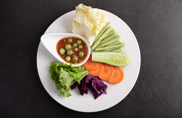 Sos krewetkowy w misce na białym talerzu z ogórkiem, fasolą szparagową, tajskim bakłażanem, smażoną białą kapustą, marchewką i sałatką