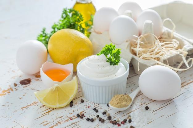 Sos majonezowy i składniki na stole z drewna