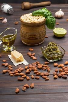 Sos pesto i składniki. orzeszki pinii nieobrane, oliwa, miseczka pesto, orzeszki pinii w drewnianym moździerzu, liście bazylii, parmezan, czosnek, cytryna. widok z góry. ciemne tło drewna