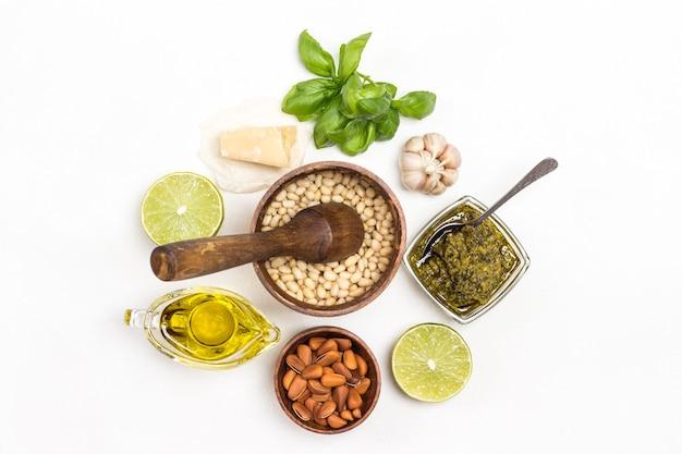 Sos pesto i składniki. orzeszki pinii w drewnianym pudełku, nieobrane orzeszki pinii w misce, oliwa z oliwek, miseczka pesto, liście bazylii, parmezan