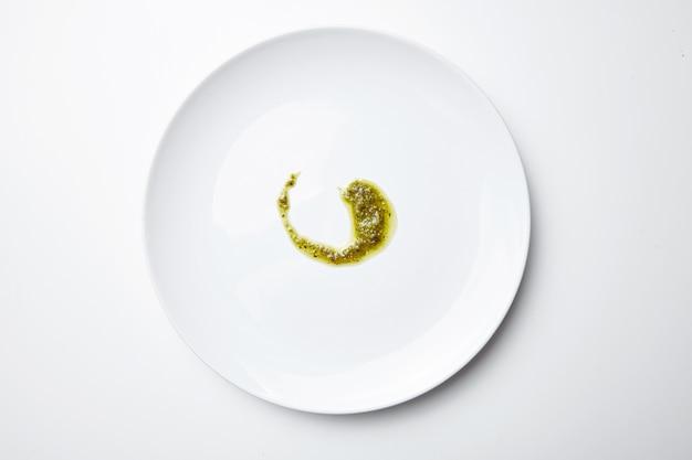 Sos pesto na białym pustym talerzu na białym tle widok z góry