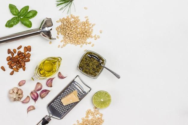 Sos pesto. orzech piniowy. trzepaczka i tarka z parmezanem. pesto w misce, liście bazylii, czosnek i cytryna.