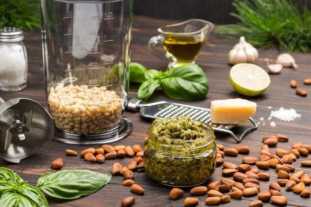 Sos pesto. słoik blendera z orzeszkami pinii. trzepaczka i tarka z parmezanem. pesto w misce, liście bazylii, czosnek i cytryna.
