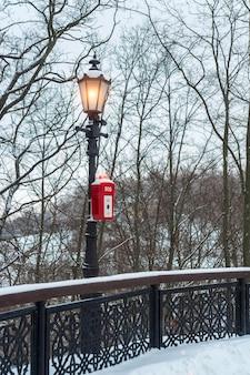 Sos policja lub przycisk alarmowy w publicznym parku pod świecącą latarnią