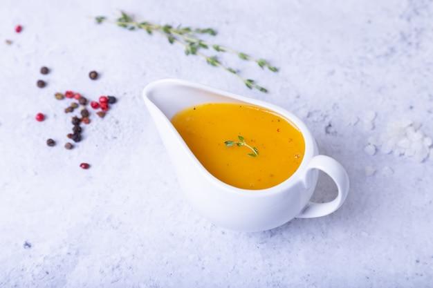 Sos pomarańczowy dla kaczki (drobiu) w białej sosie. zbliżenie, selektywne focus.