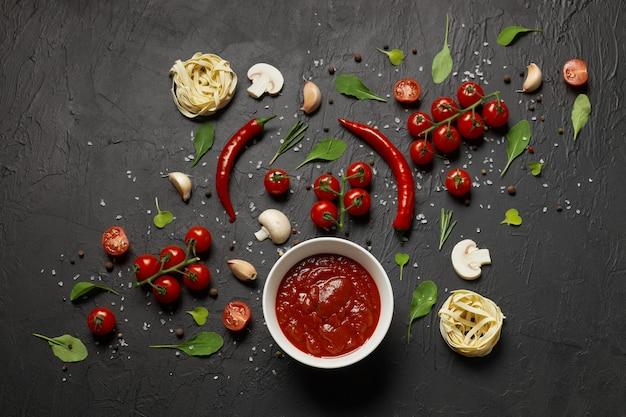 Sos pomidorowy i składniki do jego przygotowania, takie jak pomidory koktajlowe, czerwona papryka, czosnek, grzyby i przyprawy na czarno