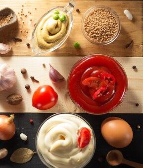 Sos pomidorowy, majonez i musztarda w misce na drewnianym tle