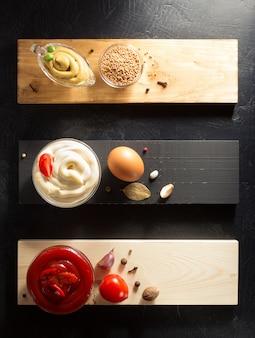 Sos pomidorowy, majonez i musztarda w misce na drewnianym