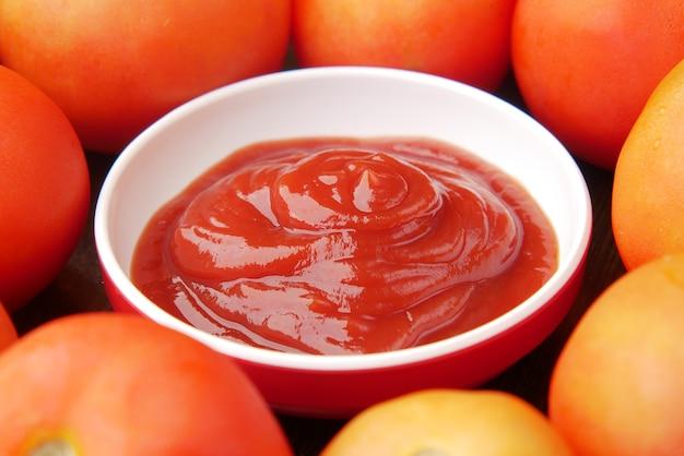 Sos pomidorowy w małym słoiczku ze świeżym pomidorem na stole
