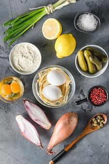 Sos ranczo w białej porcelanowej misce ze składnikami jajka kaparami, warzywami, ziołami i przyprawami na szarym kamiennym stole z teksturą.