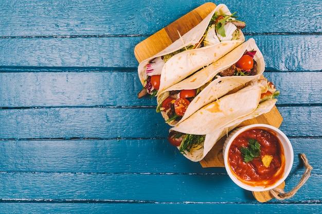 Sos salsa; meksykańskie tacos z mięsem i warzywami na deski do krojenia na niebieskim drewnianym pokładzie