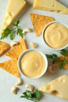 Sos serowy i przekąski na białym stole z teksturą
