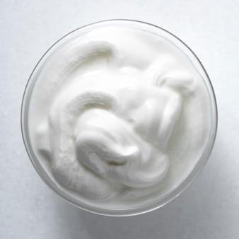 Sos śmietanowy w szklanym rondlu na białym tle.