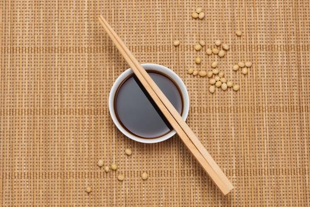 Sos sojowy i fasola sojowa z pałeczkami na drewnianym stole