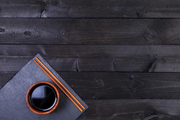 Sos sojowy, pałeczki do jedzenia na czarnym stole