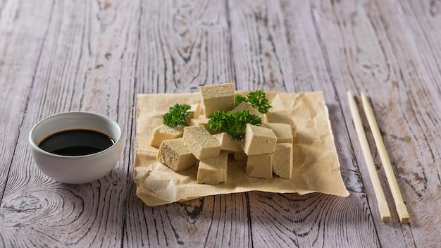 Sos sojowy z plastrami sera tofu na papierze z natką pietruszki