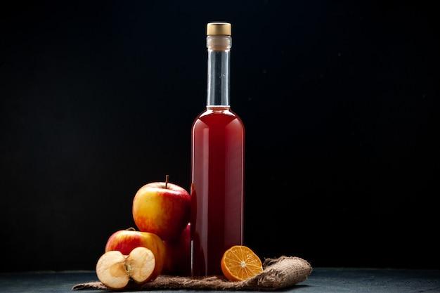 Sos z czerwonego jabłka z widokiem z przodu w butelce ze świeżymi jabłkami na ciemnej powierzchni