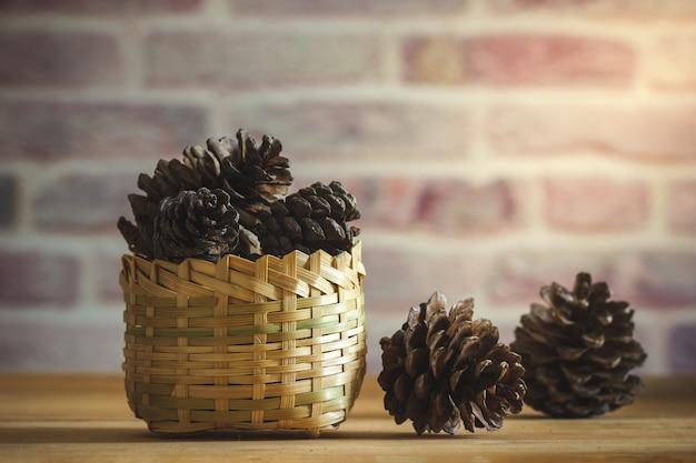 Sosna stożek w bambusowym koszu na drewnianym stole i tle ściany z cegły z porannym słońcem.