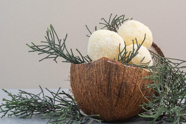 Sosnowa gałązka, smaczne kruche ciasto i kokos, na marmurze.