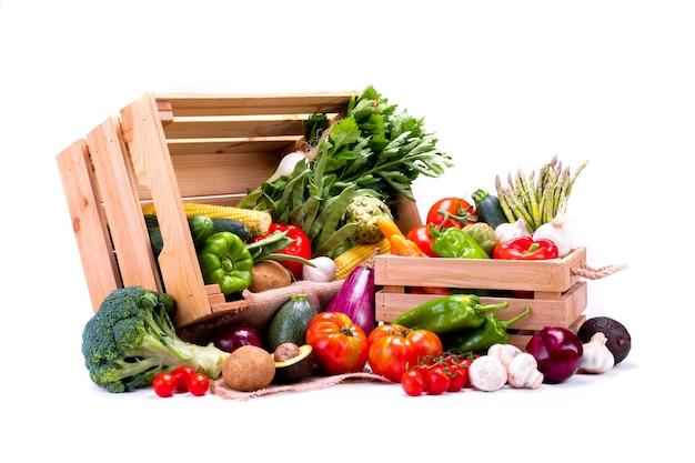 Sosnowe pudełka pełne świeżych warzyw na białym tle idealne do zbilansowanej diety