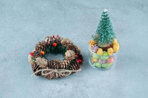 Sosnowy wieniec i pojemnik na cukierki z nogulami i figurką drzewa na marmurze.