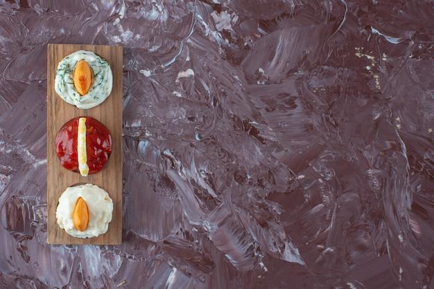 Sosy z frytkami na desce, na marmurowym stole.
