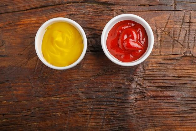 Sosy z sosem serowym i keczupem na drewnianym stole. zapisz miejsce. zdjęcie poziome