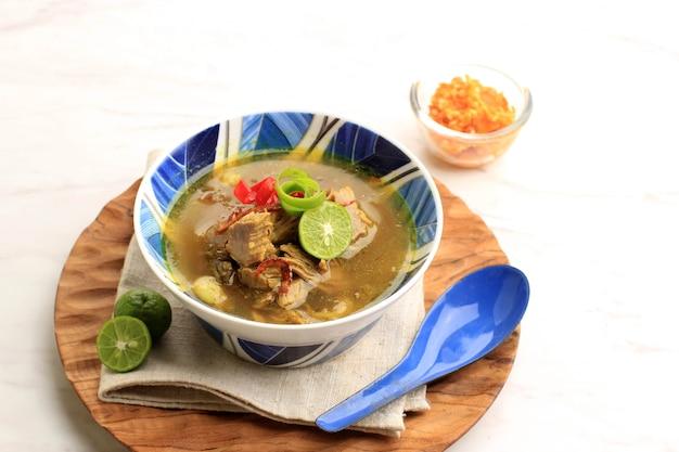 Soto sapi lub soto daging to indonezyjska zupa specjalna. to danie z bulionu wołowego z kotletem mięsnym. podawane na biało-niebieskiej misce ceramicznej. popularne menu dla idul adha