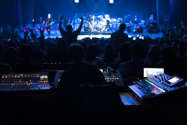 Soundman pracujący przy stole mikserskim w sali koncertowej.