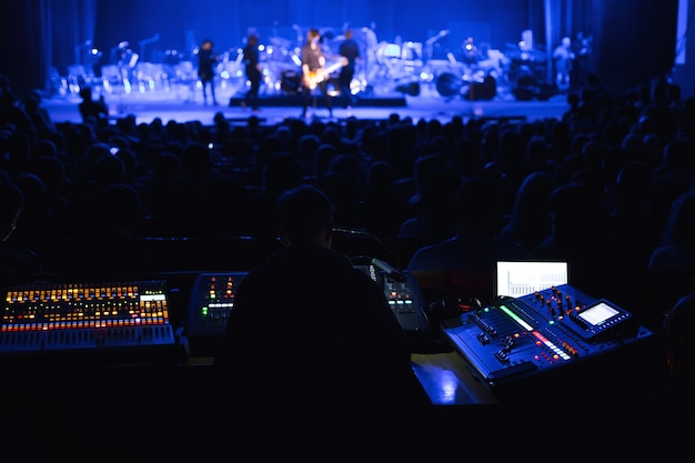 Soundman pracujący przy stole mikserskim w sali koncertowej
