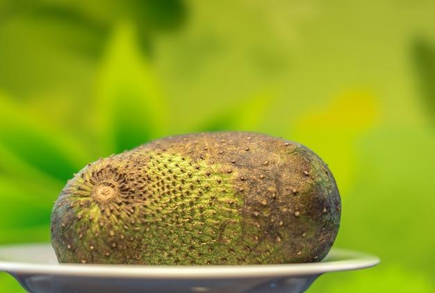 Soursop owoc pokrajać zamyka w górę zielonego tła