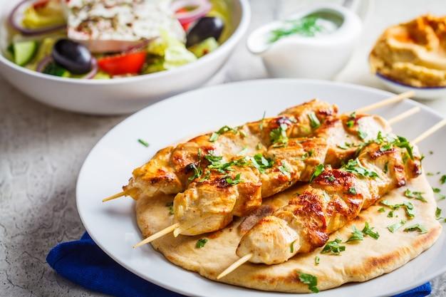 Souvlaki z kurczaka z grilla z sałatką na białym talerzu. koncepcja tradycyjnej kuchni greckiej.