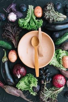 Sowa z łyżką i widelcem wśród warzyw