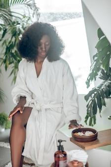 Spa. afroamerykanka w białym szlafroku z naczyniem z płatków kwiatów siedzi zamyślona w pobliżu wanny