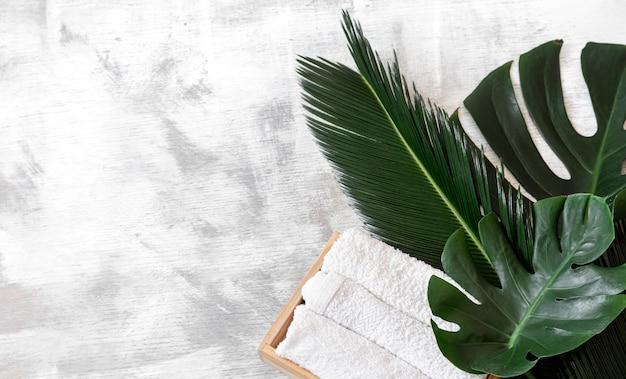 Spa. elementy do pielęgnacji ciała na białym tle z tropikalnymi liśćmi.