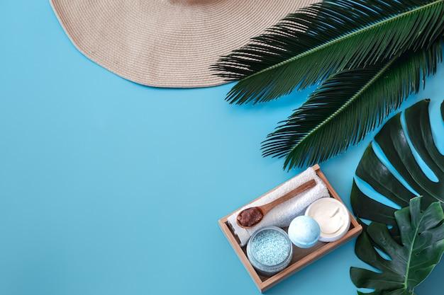 Spa. elementy do pielęgnacji ciała na niebiesko z tropikalnymi liśćmi.