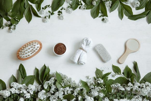 Spa flat lay kompozycja z akcesoriami kąpielowymi, produktami dla zdrowia i urody ze świeżymi kwiatami.