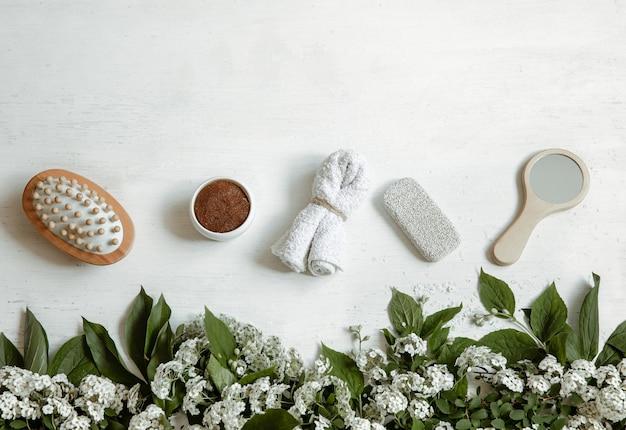 Spa flat lay kompozycja z akcesoriami kąpielowymi, produktami zdrowotnymi i pielęgnacyjnymi ze świeżymi kwiatami