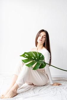 Spa i piękno. samodzielna pielęgnacja i pielęgnacja skóry. szczęśliwa piękna kobieta w przytulnych ubraniach, trzymając zielony liść monstera