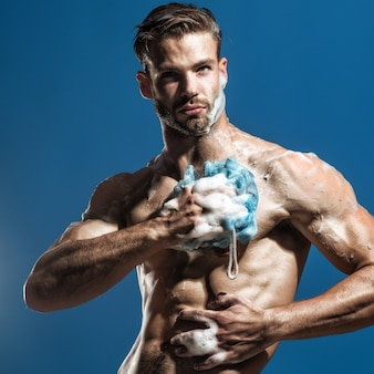 Spa i uroda relaks i higiena opieka zdrowotna przystojny mężczyzna mycie gąbką w prysznicu sportowym