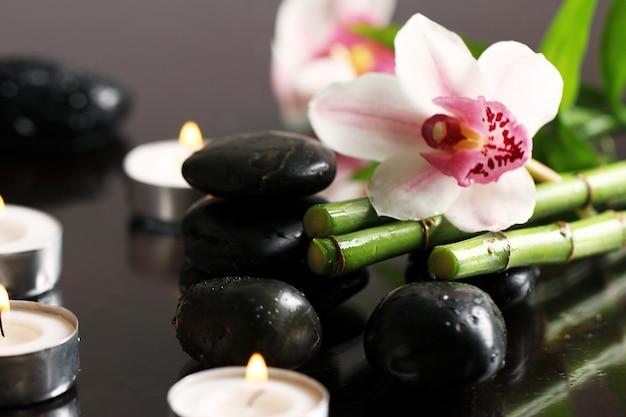 Spa i wellness, masuj kamienie i kwiaty na drewnianym obrusie