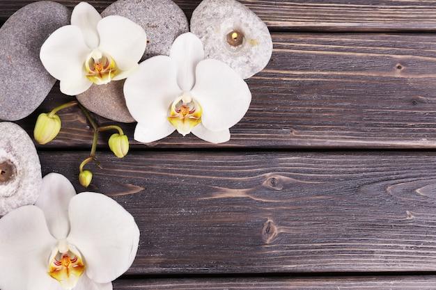Spa kamienie i kwiat orchidei na powierzchni drewnianych