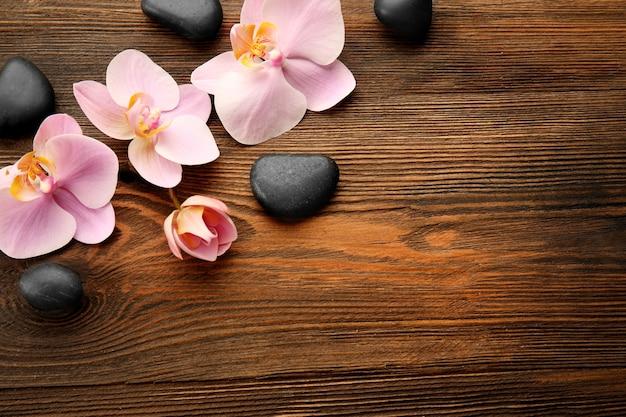 Spa kamienie i kwiaty orchidei na drewnianym stole