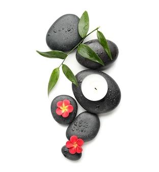 Spa kamienie, świece i kwiaty na białej powierzchni