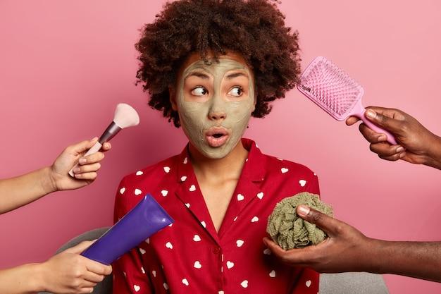 Spa, koncepcja opieki zdrowotnej. zaskoczona, czarna młoda kobieta w glinianej masce, patrzy na bok, ubrana w domową piżamę, zamierza czesać włosy