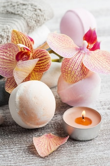 Spa martwa natura z bombami do kąpieli i czerwoną pomarańczową orchideą