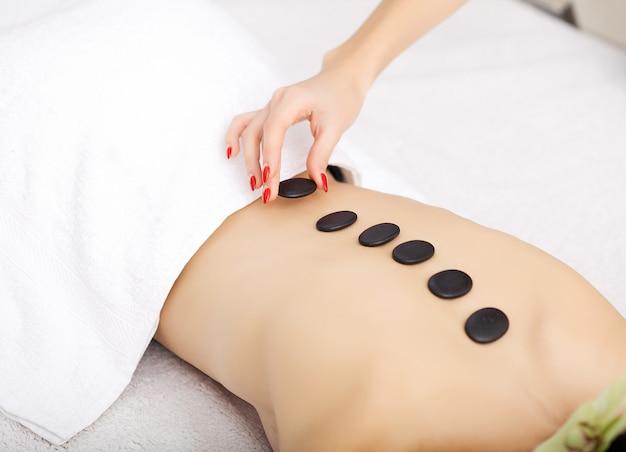 Spa. piękna kobieta spa masaż gorącymi kamieniami zabiegi kosmetyczne